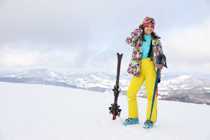 Ćwiczenia przed nartami - młoda kobieta w stroju narciarskim stojąca na stoku.